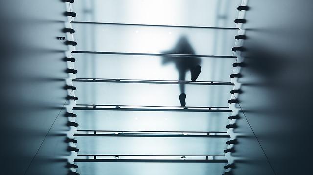Sklo, schody, silueta kráča po schodoch, pohľad zdola