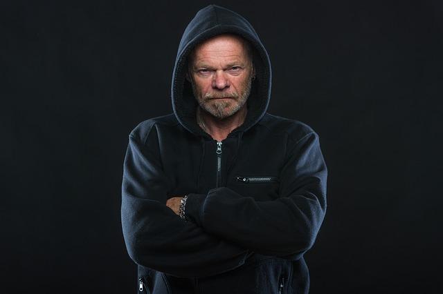 Starší muž s odhodlaním v tvári, v modrej bunde s kapucňou na hlave.jpg