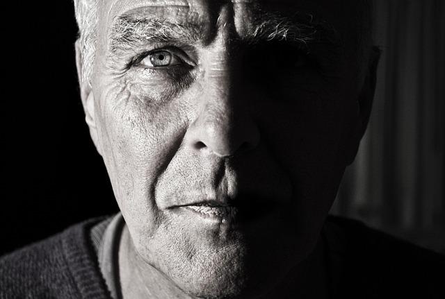 Muž vo vyššom veku s osvetlenou polovicou tváre.jpg