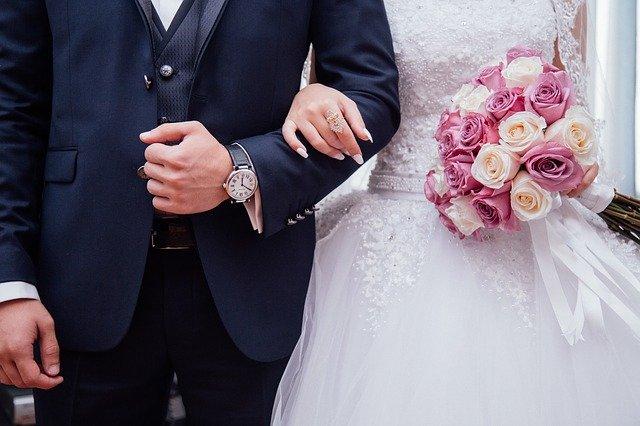 Nevesta s kyticou v ruke drží ženícha a ruku